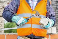 Construction worker divides brick with hammer Royalty Free Stock Images