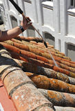 Construction worker doing cleaning the shingles with a pressurized water. Operator handling the pressure water jet to clean the shingles of lichen Stock Photo