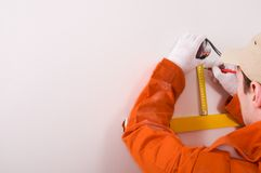 Construction worker doing measuring. Man Construction worker doing measuring Royalty Free Stock Images