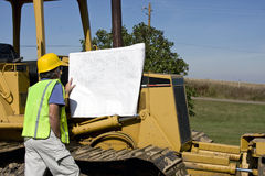 Construction worker and dozer. Construction worker looking at blueprints with a bull dozer in the background royalty free stock photos