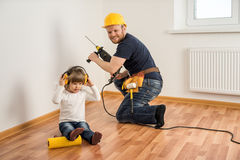 Construction worker with a drill and a little child make repairs stock photo