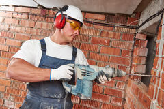 Construction worker with drill perforator. Builder worker with pneumatic hammer drill perforator equipment making hole in wall at construction site Stock Image