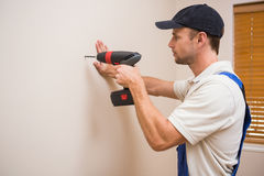 Construction worker drilling hole in wall stock images