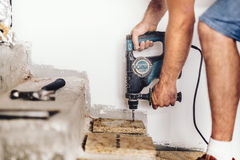 Construction worker drilling holes in wooden board and concrete using professional machinery. Industrial construction worker drilling holes in wooden board and Royalty Free Stock Images