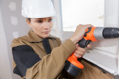 Construction worker drilling window Stock Photography