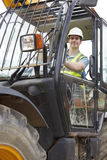 Construction Worker Driving Digger On Building Site Stock Photo