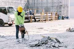 Construction worker  electric drill Drilling concrete ground in Royalty Free Stock Images