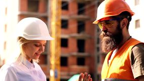Construction worker and engineer talking at construction site site. Workers in helmets at building area. Portrait of stock video footage