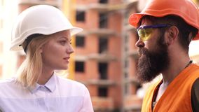 Construction worker and engineer talking at construction site site. Workers in helmets at building area. Male and female