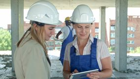 Construction worker and engineer working on building site, using digital tablet stock footage