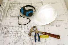 Construction worker equipments and drawing. Construction worker equipments on an engineering (architecture) drawing Stock Photos