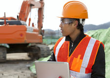 Construction worker and excavator Stock Images