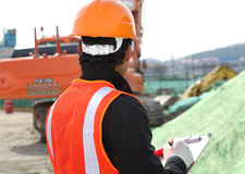 Construction worker and excavator on the background Royalty Free Stock Photo