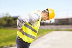 Construction worker feeling backpain in lumbar area. Pressing painful lower back and leaning forward stock photography