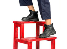 Construction worker feet. On red stairs  isolated on white background Royalty Free Stock Images