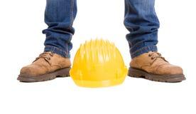 Construction worker feet and yellow helmet Stock Photos