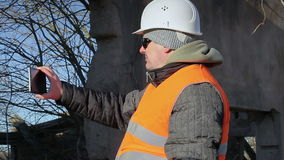 Construction worker filmed with tablet PC. Winter  day stock footage