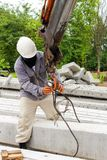 Construction worker fitting crane hook on pole Stock Photography