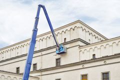 Construction worker fixing house facade using lifting boom machinery. Construction worker fixing house facade using blue lifting boom machinery Royalty Free Stock Photography