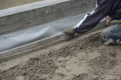 Construction worker flattening the cement floor. Construction worker kneeling, flattening the cement floor with a hand leveler Stock Images