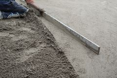 Construction worker flattening the cement floor. Construction worker kneeling, flattening the cement floor with a hand leveler Royalty Free Stock Images