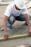 Construction worker flattening slab Stock Image