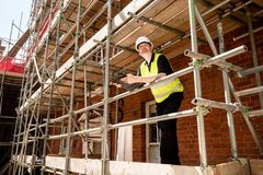 Construction worker, foreman or architect on scaffolding at construction site with clipboard. Male construction worker, foreman or architect on scaffolding at stock image