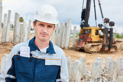 Construction worker foreman in front of pile driver machine. Builder worker foreman of pile driver machine at construction building site royalty free stock photography