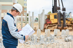 Construction worker foreman in front of pile driver machine. Builder worker foreman of pile driver machine at construction building site stock photos