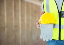 Construction Worker in front of construction site. Digital composite of Construction Worker in front of construction site Royalty Free Stock Images