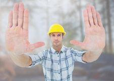 Construction Worker gesturing stop hands in front of construction site. Digital composite of Construction Worker gesturing stop hands in front of construction Stock Photography