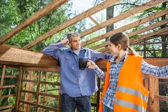 Construction Worker Giving Coffee To Colleague Stock Image