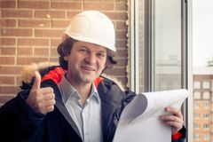 A construction worker giving his thumbs-up in front of a newly constructed residential building. Soft focus, toned. stock photo