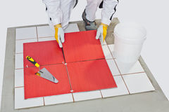 Construction worker glued ceramic tile floor Royalty Free Stock Image
