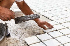 Construction worker glued ceramic tile floor Royalty Free Stock Photo