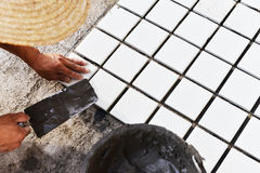 Construction worker glued ceramic tile floor Stock Photos
