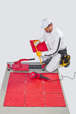 Construction worker glued red ceramic tile Royalty Free Stock Image