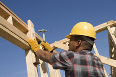 Construction Worker Hammering Nail On Timber Frame Royalty Free Stock Image
