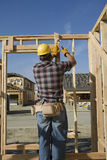 Construction Worker Hammering Nail On Timber Frame Stock Photo