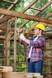 Construction Worker Hammering Nail On Wooden Cabin Royalty Free Stock Images