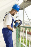 A construction worker with a hand grinder cuts the steel rod on construction site Royalty Free Stock Photography