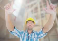 Construction Worker with hands up in air in front of construction site Royalty Free Stock Images