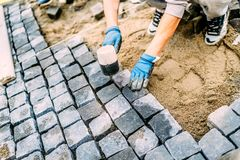 Construction worker, handyman using cobblestone granite stones for creating walking path. Terrace or sidewalk details. Industrial construction worker, handyman stock photo