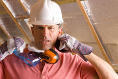 Construction worker with hard hat, goggles and ear protectors Stock Photos