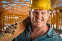 Construction Worker in Hard Hat Holding Plank of Wood At Worksite. Smiling Contractor in Hard Hat Holding Plank of Wood At Construction Site royalty free stock images