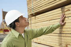 Construction Worker In Hardhat Inspecting Lumber. Side view of a smiling construction worker in hardhat inspecting lumber on job site Stock Photo