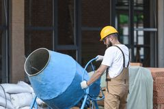Construction worker in hardhat and protective googles working with concrete mixer on construction. Site stock photography