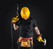 Construction worker in helmet with hammer and drill. On dark background Royalty Free Stock Photo