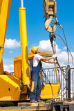 Construction worker during hoisting works by a mobile crane. Industrial worker in uniform and protective gear during hoisting works by a mobile crane Stock Photo
