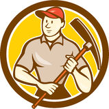 Construction Worker Holding Pickaxe Circle Cartoon. Illustration of a construction worker wearing hat holding pickaxe set inside circle on isolated background Royalty Free Stock Photo